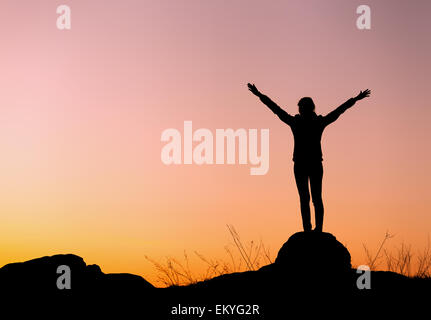 Silhouette of happy young woman with arms raised up against beautiful colorful sky. Summer Sunset. Landscape - Stock Photo