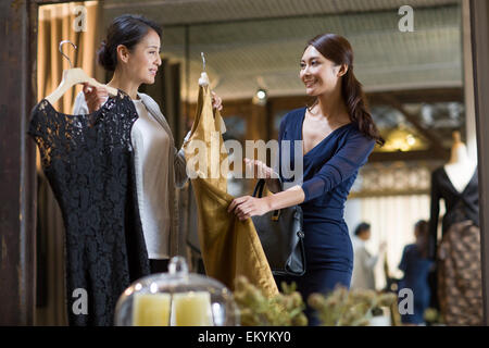 Clothing store owner helping customer with choosing dress - Stock Photo