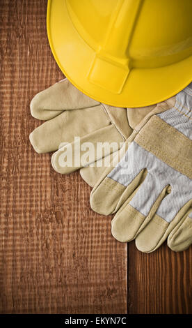 view on a hardhat with gloves on wooden board - Stock Photo