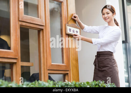 Young waitress with open sign in restaurant doorway - Stock Photo