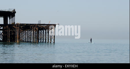 Brighton Sussex UK 15th April 2015 - A man fishes from his paddle board by the West Pier Brighton in beautiful weather - Stock Photo