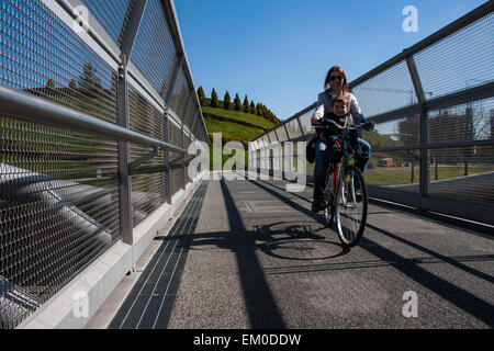 Modern steel cycle bridge that connects the city park - Stock Photo