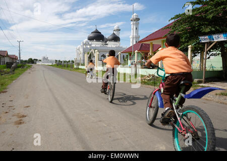 School children cycling along the road in front of a small mosque, near Banda Aceh; Aceh Province, Sumatra, Indonesia - Stock Photo
