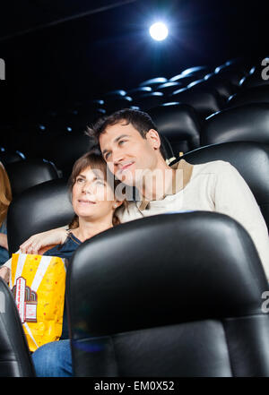 Affectionate Couple Watching Film In Theater - Stock Photo