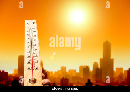 heat wave in the city and hand showing thermometer for high temp - Stock Photo