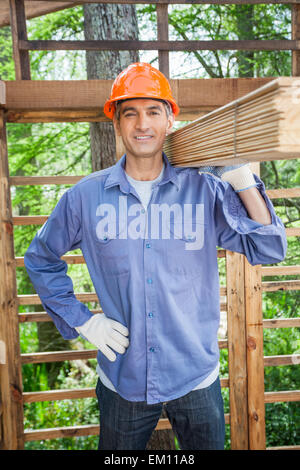 Confident Worker Carrying Tied Wooden Planks - Stock Photo