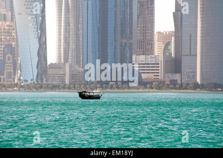 A dhow boat plows the waters of the Arabian Gulf near the skyline of Doha, the capital of Gulf nation of Qatar. - Stock Photo