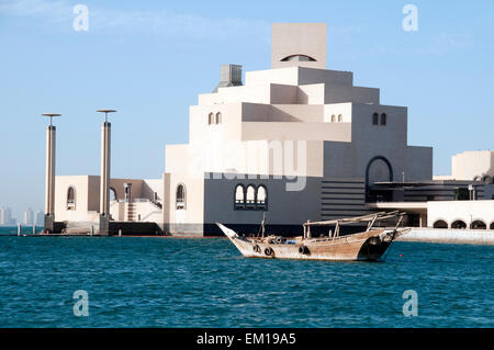 A dhow boat floats on the Arabian Gulf in front of the Museum of Islamic Art in Doha, Qatar. - Stock Photo
