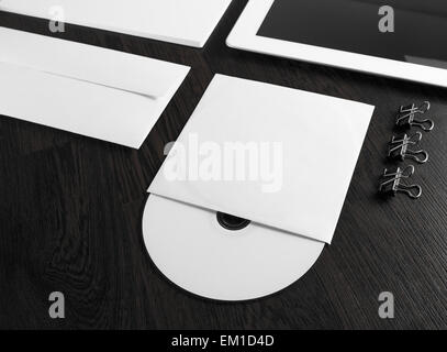 Blank compact disk on wooden table. Fragment of blank stationery and corporate identity template on dark background. - Stock Photo