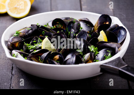 Fresh mussels cooked in a pan with wine and herbs - Stock Photo