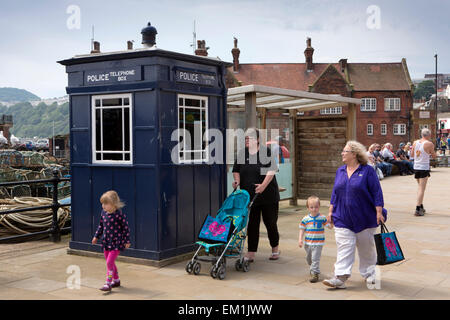 UK, England, Yorkshire, Scarborough, Sandside visitors walking past seafront Tardis Blue police call box - Stock Photo
