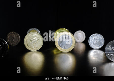 A selection of metal coins from the UK, Europe and South Africa photographed against a black background. - Stock Photo