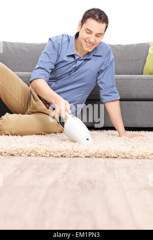 Vertical shot of a young cheerful man cleaning a carpet with a handheld vacuum cleaner in  front of a gray sofa - Stock Photo