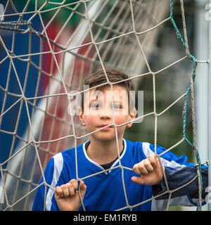 Little football player behind the football goal. - Stock Photo