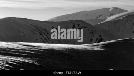 black and white photography. strong storm, one person goes in high snow-capped mountain ranges, from the man falls - Stock Photo