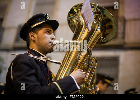 Horn player in a marching band at a night time procession during Semana Santa (Holy Week) in Jumilla, Spain - Stock Photo
