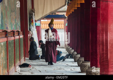 A monk carrying an artifact of Buddhist praying ceremony at Labrang Monastery of Tibet; Tibet, China - Stock Photo