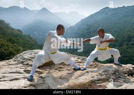 Monks of the Songshan Shaolin Temple perform near Shaoshi Mountain, Zhengzhou, Dengeng County, Henan Province, China - Stock Photo