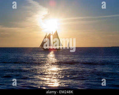 Sailboat with sightseers off Mallory Square during daily sunset celebration, Key West, Florida. - Stock Photo