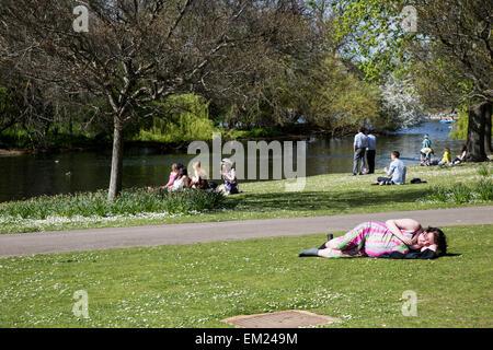 Woman Sunbathing in Regents Park London UK - Stock Photo