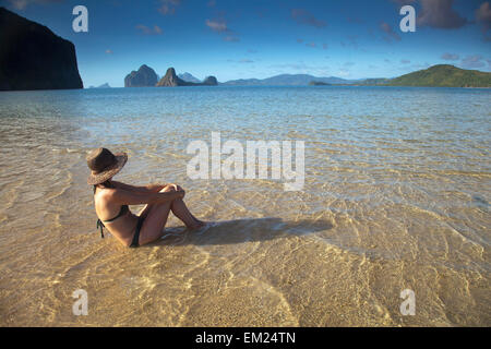 A Woman Tourist In A Bikini Sits In Shallow Water Near El Nido And Corong Corong; Bacuit Archipelago Palawan Philippines - Stock Photo