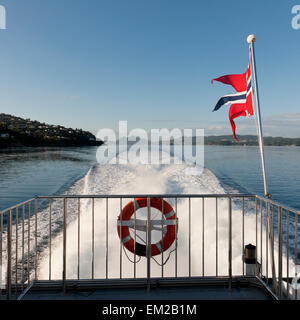 Flag Of Norway Flying On The Back Of A Boat; Sognefjord Norway - Stock Photo