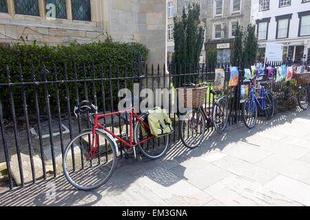 Bikes against church railings in Cambridge, UK - Stock Photo