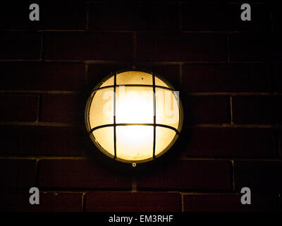 turn on outdoor lamp on brick wall - Stock Photo