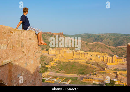 A Young Man Sits Barefoot On The Top Of A Wall Looking Out Over The Amer Fort; Jaipur Rajasthan India - Stock Photo