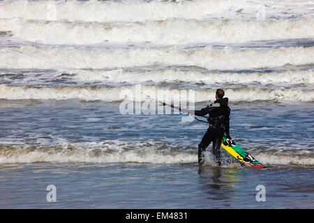A Kitesurfer Stands Watching The Waves Come In; Tynemouth Tyne And Wear England - Stock Photo