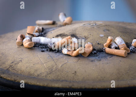 Cigarette butts in an exterior ashtray - Stock Photo