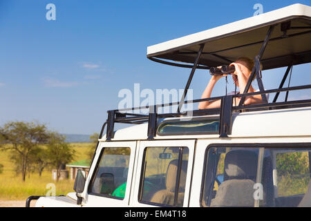 Woman on safari looking through binoculars. - Stock Photo