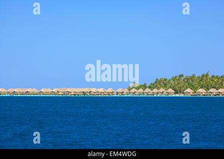 A Resort Along The Coast Of Motu Paahi Near Bora Bora Airport; Society Islands French Polynesia South Pacific - Stock Photo