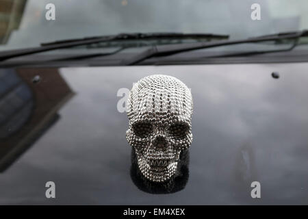 Metallic skull bonnet badge on the hood of a taxi. This small human head is styled on the Damien Hirst diamond skull, - Stock Photo