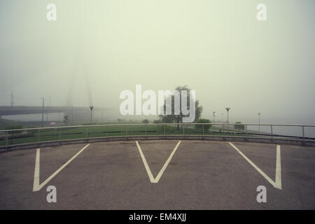 Parking lines on the background of the park and river bridge in the fog. Riga, Latvia - Stock Photo