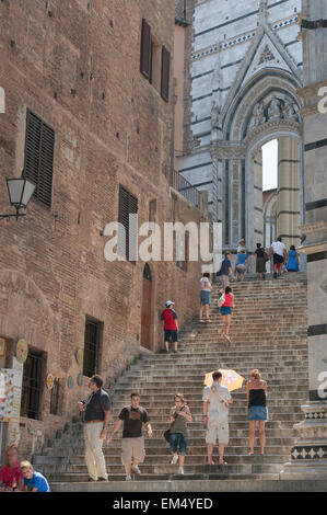 Italy tourism, view in summer of tourists ascending the stairway to the west end of the Duomo (cathedral) in Siena, - Stock Photo