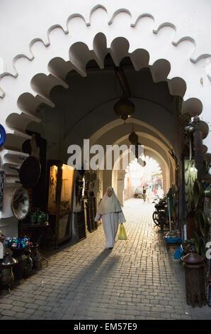 Morocco, Marrakech, Medina, Woman walking with shopping bag through covered corridor - Stock Photo