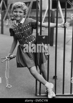 1950s 7 Year Old Girl Wearing Dress Sit On Seesaw Teeter