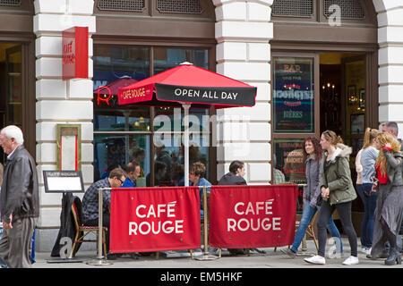 People enjoy Alfresco dining outside Cafe Rouge in the warm sunshine - Stock Photo