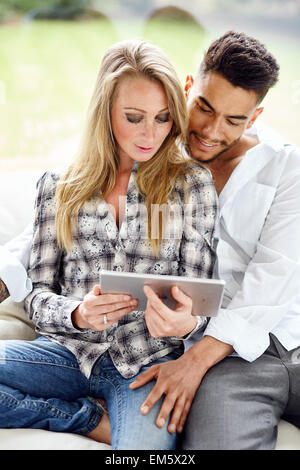 Couple looking at an iPad together - Stock Photo