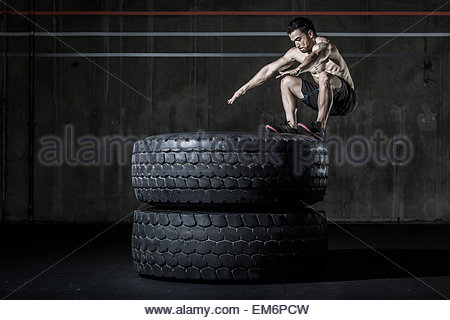 A shirtless male weightlifter and CrossFit athlete performing a box jump on two tires  in a CrossFit gym. - Stock Photo