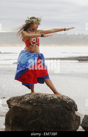 USA, Hawaii Islands, Maui, Beautiful Hawaiian girl dancing hula on rock overlooking ocean; La Perouse Bay - Stock Photo