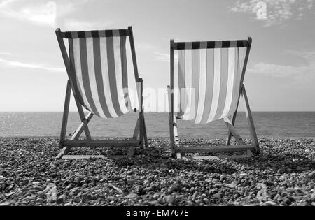 Brighton Beach, Deck chairs on the beach with single sailing boat in the background black and white - Stock Photo