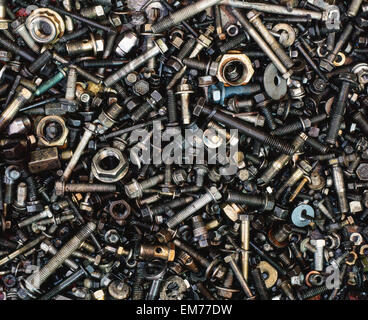 A sea of nuts and bolts of various sizes and color. A heap pile of industrial hardware for machinery repairs. - Stock Photo