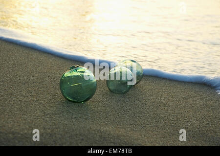 Three Glass Fishing Floats Rest On The Sandy Shoreline - Stock Photo