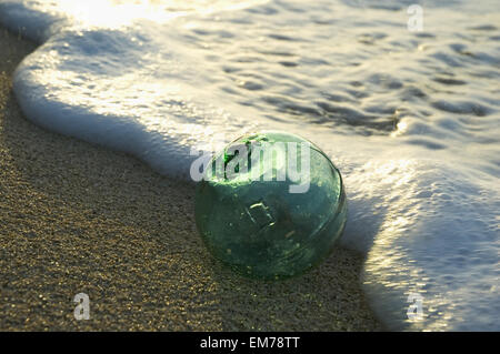 A Glass Fishing Float Rolls On The Sandy Shoreline With Ripples Of Water And Seafoam - Stock Photo