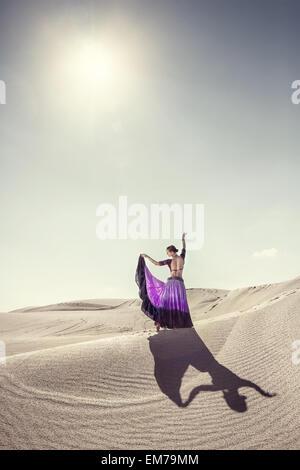 Woman in violet skirt dancing in the desert - Stock Photo