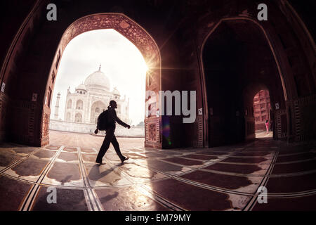 Tourist with backpack walking in the mosque arch near Taj Mahal in Agra, Uttar Pradesh, India - Stock Photo