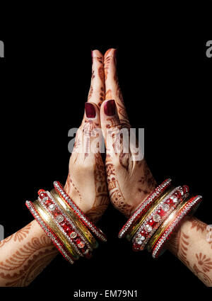 Woman hands with henna in Namaste mudra on black background - Stock Photo