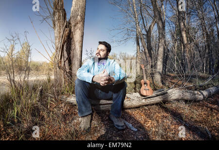 Man in blue shirt with bow tie and ukulele on the tree trunk in the forest - Stock Photo
